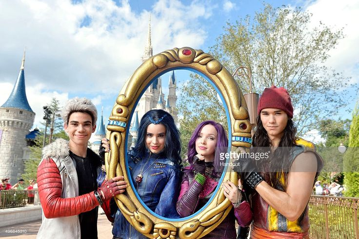 In this handout provided by Disney Parks, The cast of Disney Channel Original Movie 'Descendants' (L-R) Cameron Boyce who plays Carlos, Sofia Carson who plays Evie, Dove Cameron who plays Mal and Booboo Stewart who plays Jay pose during a break from taping the Disney Parks Unforgettable Christmas Celebration TV special in Magic Kingdom park at Walt Disney World Resort November 10, 2015 in Lake Buena Vista, Florida. The 32nd annual holiday telecast airs nationwide Dec. 25 on ABC-TV.