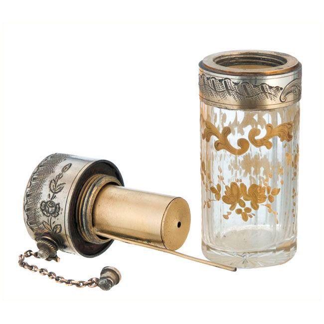FRASCO PERFUMERO EN CRISTAL En plata repujada con adornos florales.Ornamentos en oro. Tapón en metal.Bomba de vacío.Medidas: 9 x 4 cm.