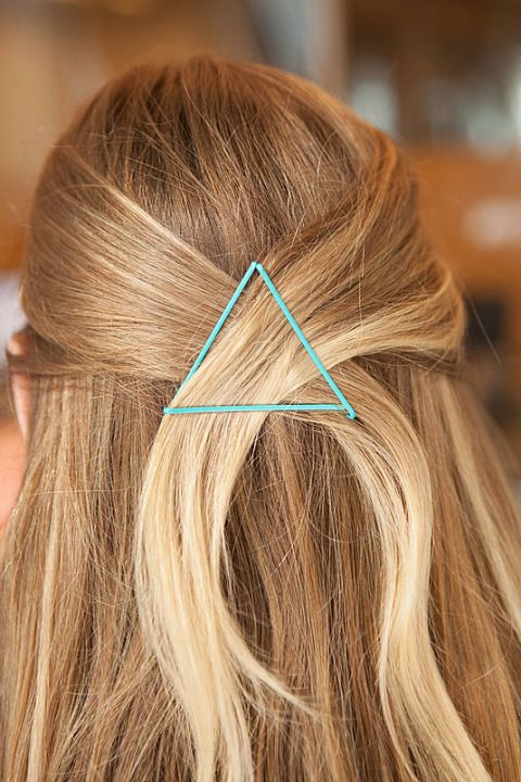 take a bobby pin and slide it in horizontally over the crossed section. Then take another bobby pin and slide it upward at a diagonal angle to set the right side. Repeat this on the left to complete the triangle