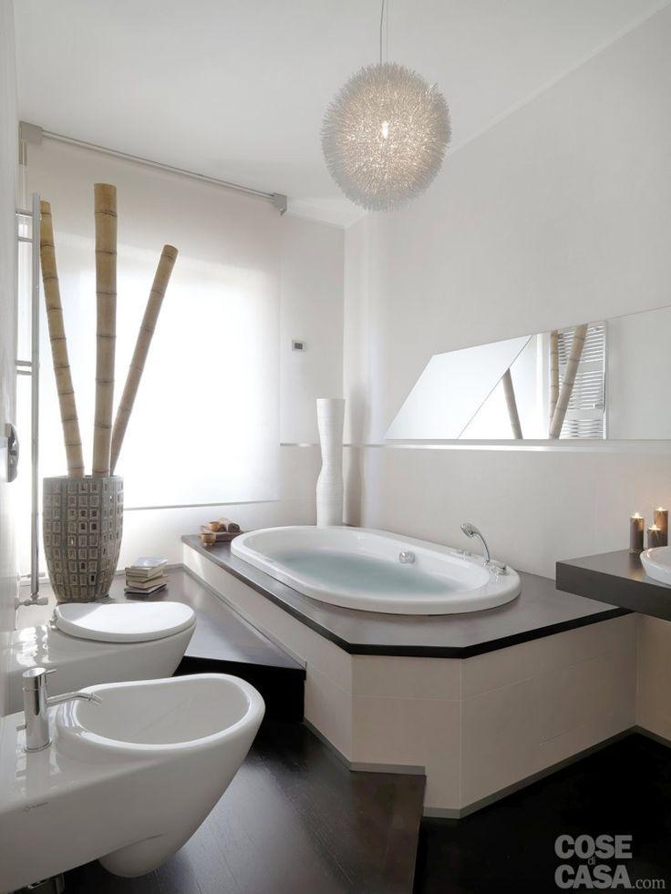 Nel #bagno a uso esclusivo della camera la pedana con la vasca #idromassaggio sfrutta l'altezza del sottofinestra; di lato, sulla parete, è fissato uno specchio sagomato privo di cornice. Il sopralzo sul quale sono installati i sanitari consente di ottenere la pendenza necessaria per gli scarichi. • Vasca idromassaggio: Opalia di Jacuzzi • Sanitari: Ceramica Flaminia • Lampada a sospensione: Star SP20 di Ideal Lux