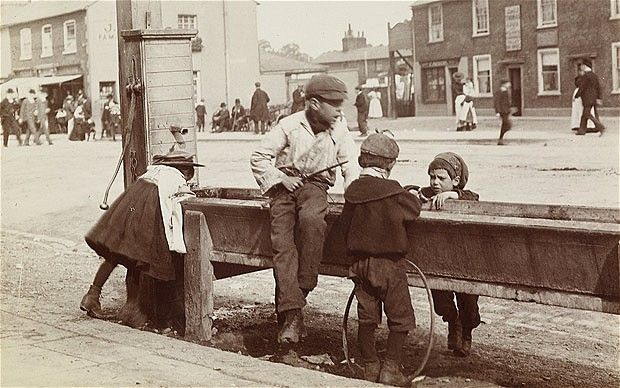 This photo looks like it was taken in a small town rather than in London, but it shows children playing at a water trough on Barnet High Street, from around 1900. One, you'll notice, has a hoop propped against the trough's side. The photographer is unknown.
