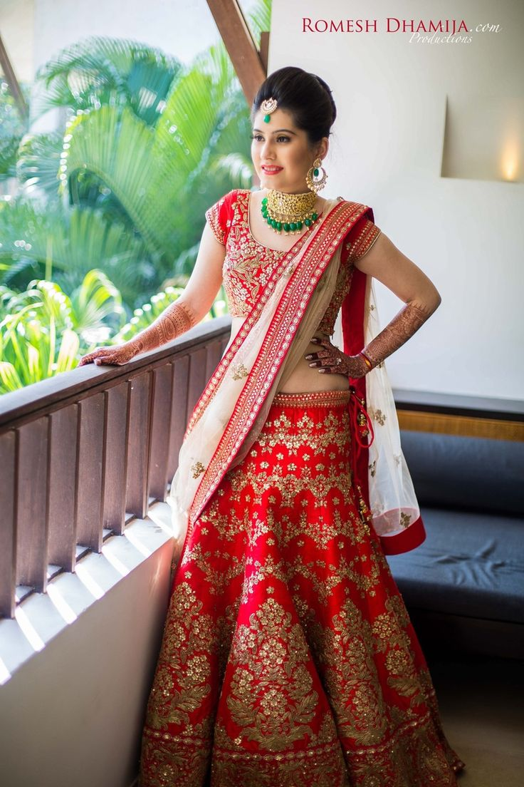 Real Indian Weddings - Kritika and Punit | WedMeGood | Bride in a Coral Red and Golden Embroidered Bridal Lehenga and Cream Dupatta with Gold and Emerald Jewelry Picture Courtesy: @romeshdhamija #wedmegood #realwedding #bridal #lehenga