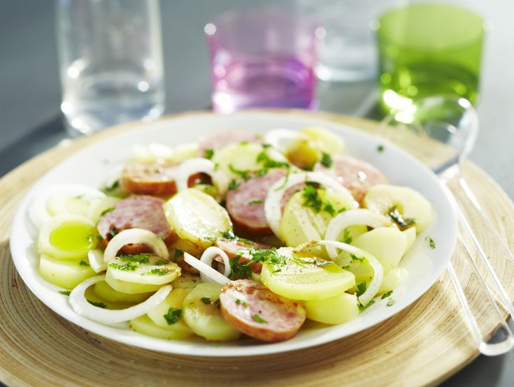 Epluchez les pommes de terre. Coupez-les en rondelles. Dans 1 litre d'eau bouillante, faites dissoudre les cubes de bouillon goût Pot-au-Feu. Jetez-y les rondelles de pommes de terre et la saucisse. Laissez-les cuire 10 minutes. Egouttez-les. Coupez les oignons en rondelles. Préparez la vinaigrette avec l'huile, le vinaigre et le poivre. Mélangez ensemble les pommes de terre encore chaudes, la vinaigrette, les oignons et les tranches de saucisson. Saupoudrez de persil.