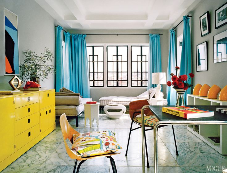 Josef Frankinspired pillows on 1950s Pierre Guariche chairs and a citron 1970s lacquered sideboard, found at Paul Smith in London, infuse the study with pops of color.