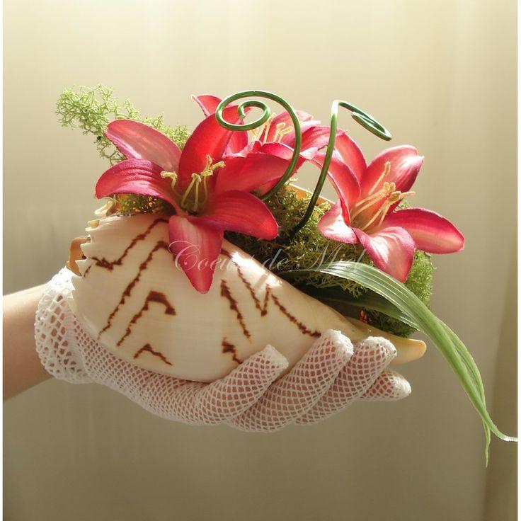 Nacré, ce porte alliance sera idéal pour un mariage au thème exotique et plage. Réalisé à partir d'un coquillage, ce coussin d'alliance est orné de fleurs de lys fuchsia et de mousse végétale. Vous pourrez y maintenir vos alliances grâce à deux arabesques vertes.