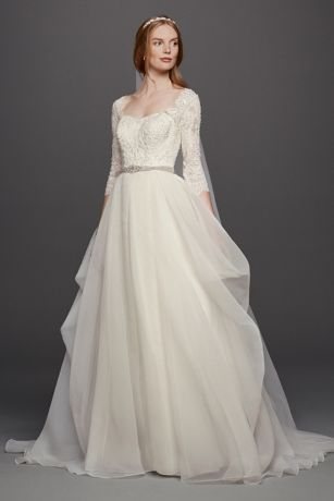 organza ball gown with demure three-quarter lace sleeves and a flattering sweetheart neckline. The draping of the tulle skirt