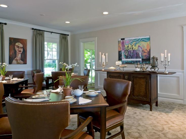 This traditional dining room features a buffet set with coffee and dessert, along with neutral-colored walls, carpet, furniture and decor. Abstract paintings add a small pop of color.