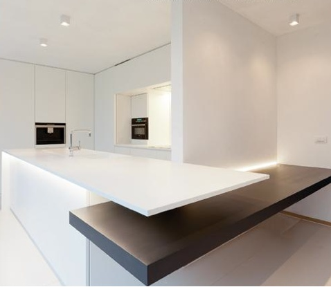Minimal kitchen with an extra-large countertop by Belgian interior designer Filip Deslee _