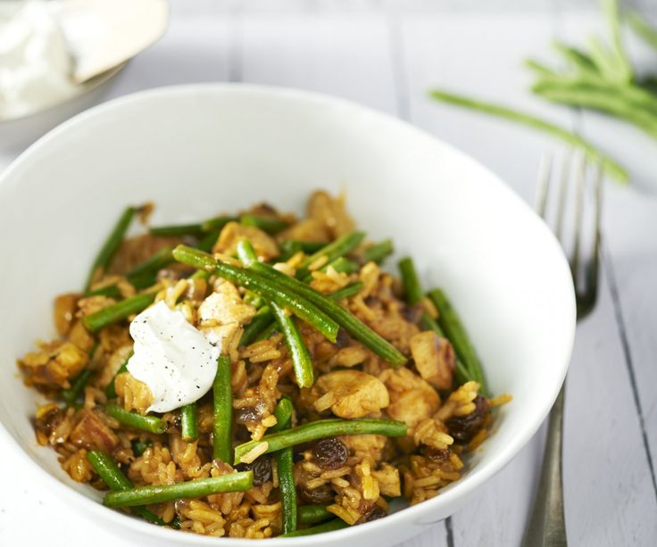 Biryani di pollo con fagiolini. Il Biryani è un piatto di riso con pollo, tipico della cucina indiana, che è deliziosamente speziato e facile da preparare. Lo yogurt fresco contrasta benissimo con questo piatto piccante. È la pietanza perfetta per una serata movimentata!