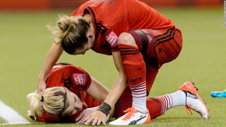 Alexandra Popp, left, of Germany suffers a head injury and is checked on by Simone Laudehr.