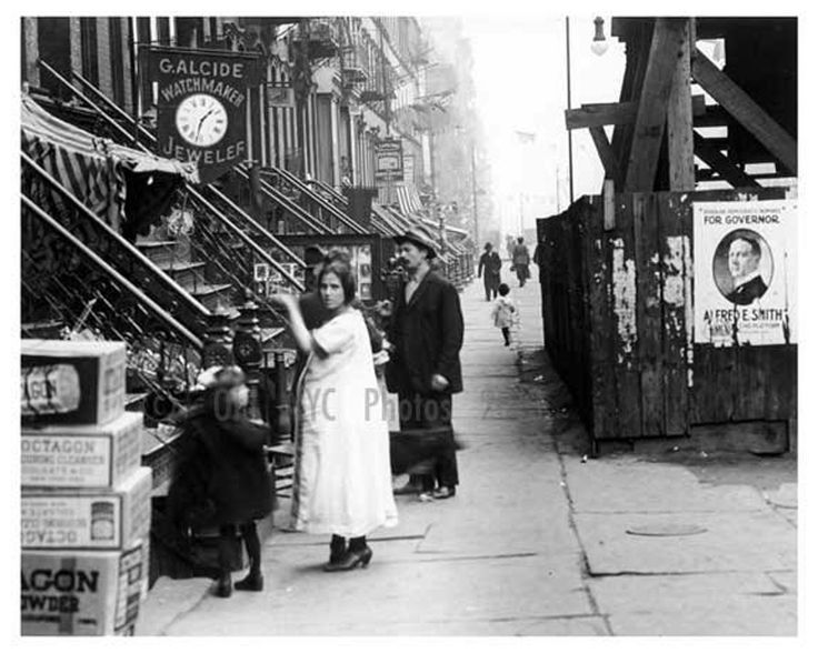 East 14th St. East Village, what appears to be a pregnant lady weighing produce. Love the campaign poster for Al Smith. 1918 oldnycphotos.
