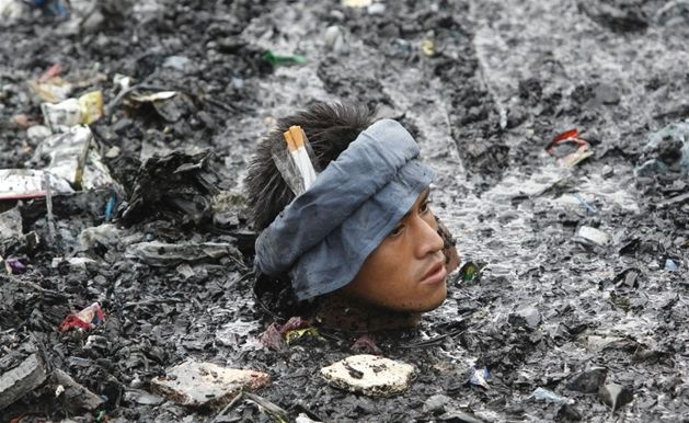 Mężczyzna szuka cennych rzeczy wśród zgliszczy po pożarze wioski Malabon na Filipinach, 7 kwietnia. Fot. ERIK DE CASTRO/REUTERS/forum