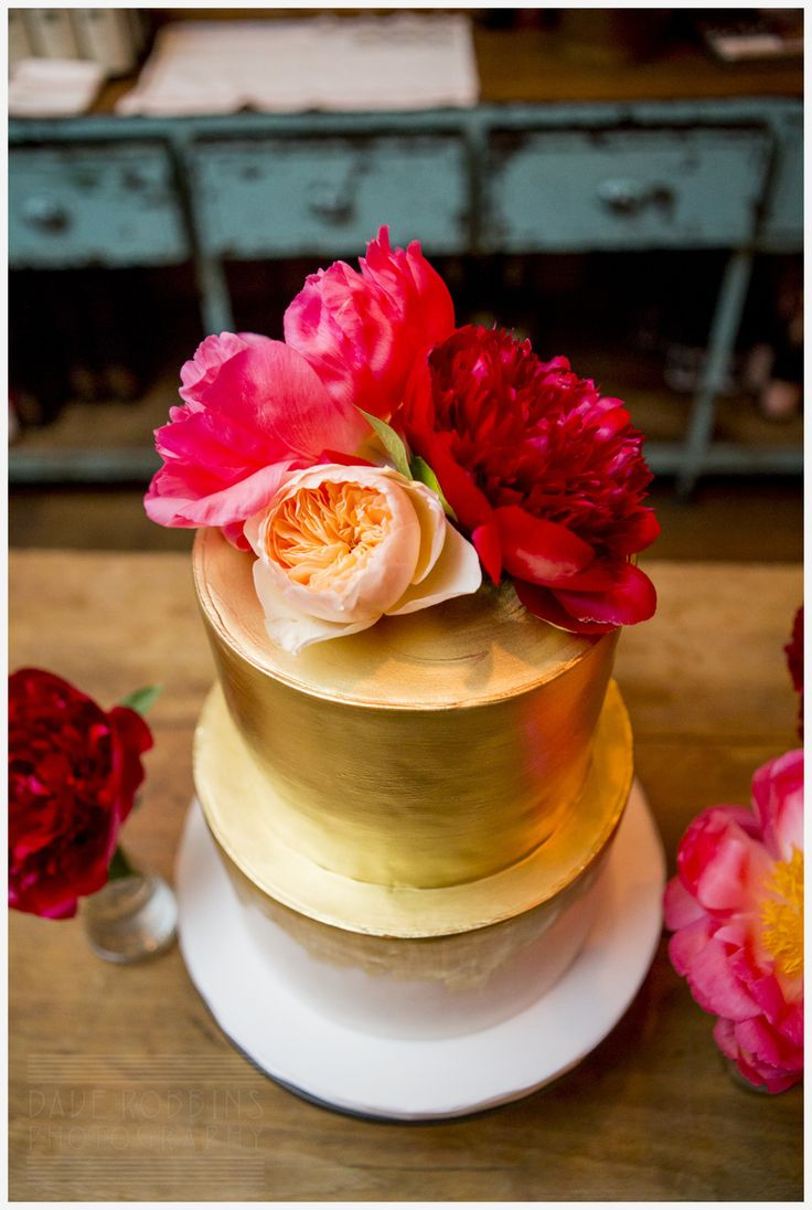 Chic gold-brushed wedding cake topped with bright fuchsia, red and peach flowers