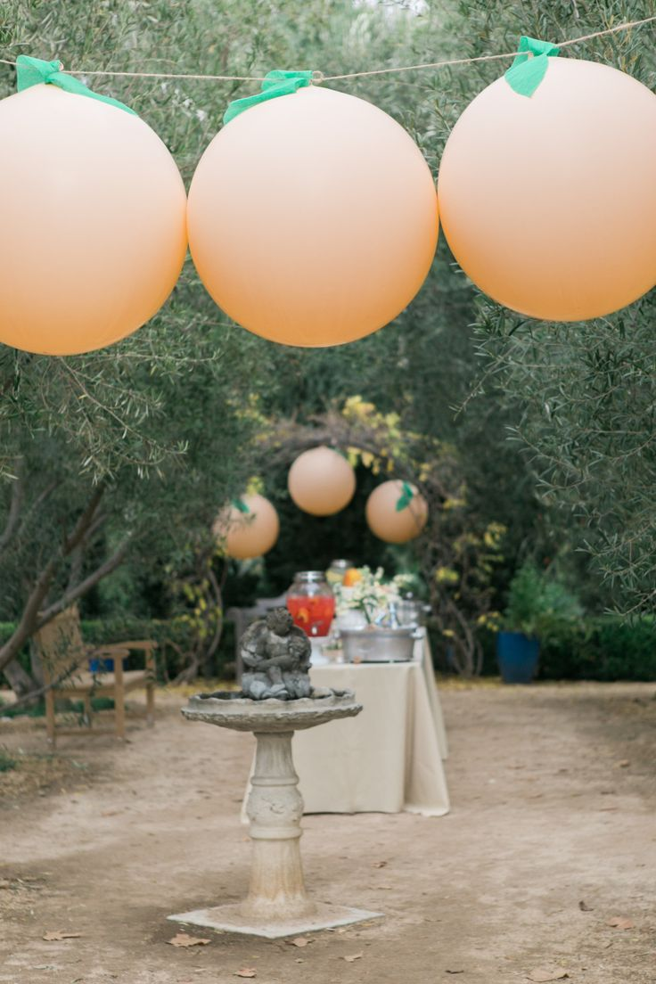 This James and the Giant Peach brunch decor, created by @twinkandsis and captured in these stunning photographs by Jenna Elliott for @SMPliving, is the most peach-perfect party idea we've seen!   Twink & Sis used giant balloons, with green crepe paper leaves (cut out themselves), to give the effect of peaches floating overhead. Click through for more stunning party ideas.
