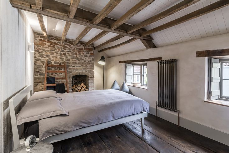 Miner's Cottage II - master bedroom in an eighteenth century cottage with exposed beams, shutters, wide elm floorboards, lime plaster walls, exposed stone fireplace, reclaimed timber feature wall