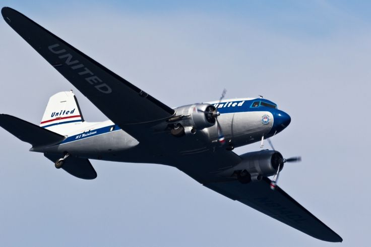 A photo of a United Airlines McDonald Douglass DC-3 airplane owned by Clay Lacy Aviation, doing a fly by during the an air show at Catalina Island. The aircraft registration is N814CL