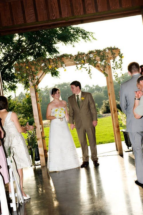 Beautiful light wood arbor - perfect for a summer wedding outdoors! I like the ivy looking flowers hanging off!