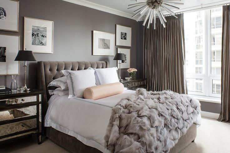 Glamorous gray bedroom features walls painted dark gray lined with a dark gray velvet tufted bed dressed in black and white hotel bedding, gray faux fur blanket and a pale pink bolster pillow flanked by mirrored nightstands under collections of art.