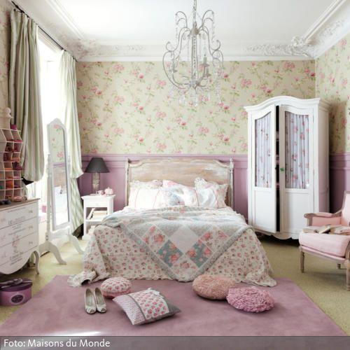 Fantastisch! Zur Hälfte rosafarbene Wände und oberhalb eine Tapete mit Blumenmuster, dazu ein rosafarbener Teppich und Blümchen-Bettwäsche: Fast wirkt das mädchenhafte Schlafzimmer wie ein niedlich eingerichtetes Puppenhaus. Die romantische Note des Zimmers wird durch den Kronleuchter und die antiken Holzmöbel noch verstärkt.
