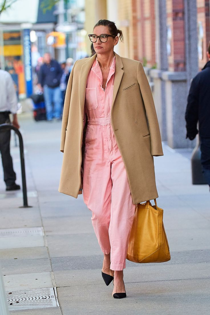 Jenna Lyons in a pink jumpsuit, camel coat, mustard tote and black pointy toe heels.