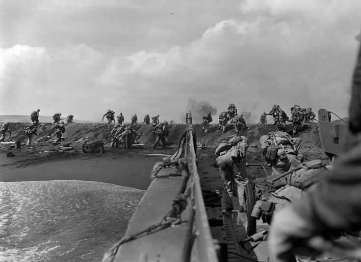 In the Pacific theater of World War II, U.S. Marines hit the beach and charge over a dune on Iwo Jima in the Volcano Islands during the start of one of the deadliest battles of the war against Japan.