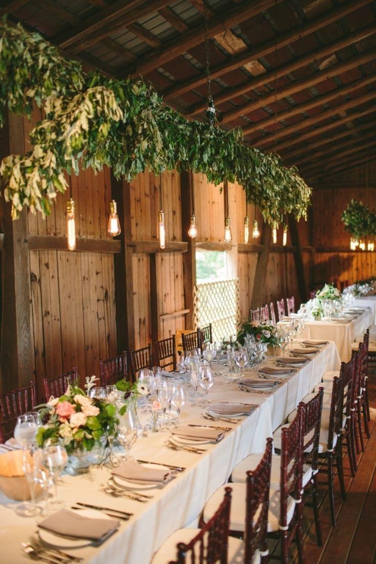 Hanging lights and long tables gussy up a #barn reception | Design: www.oleanderbotanicals.com