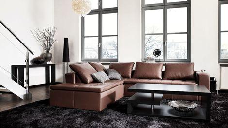 Skinnsofa i brunt og et stort, nesten heldekkende teppe gjør rommet lunt.