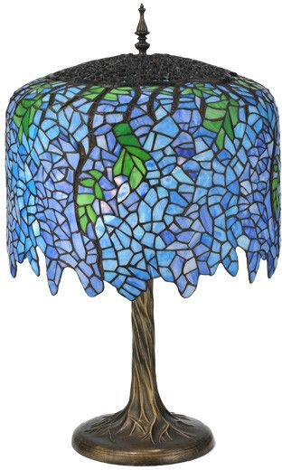 Cascading blossoms in varigated hues of Blue glasswith Spring Green leaves were favored subjects of theL. C. Tiffany Studio. This beautiful Wisteria stainedglass shade with undulating border, is paired with anatural-looking tree trunk base in an antique p