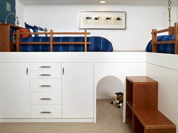 The loft-style beds in this boys' room have plenty of storage and a play area underneath, making the space appear larger.