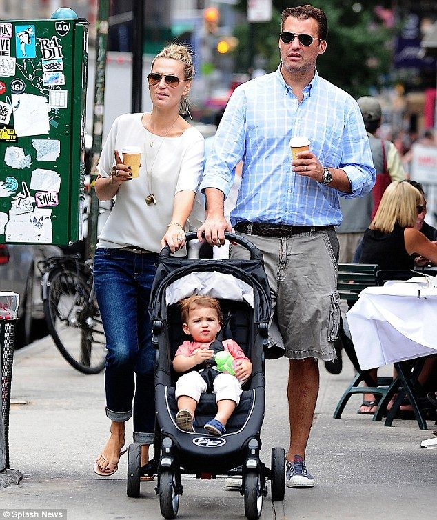 Molly Simms and Scott Stuber sip on drinks as they go for a stroll with son Brooks in Soho