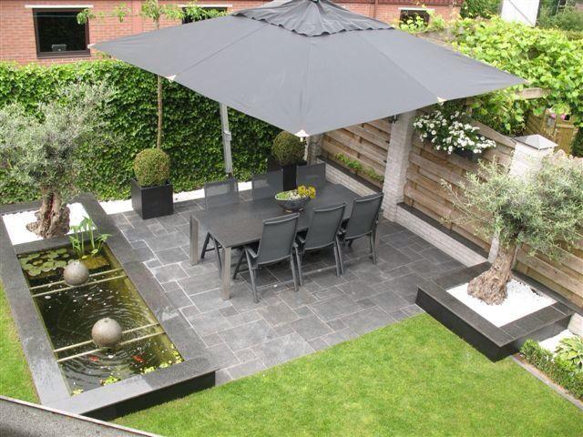 Mooi terras met grote paraplu... Natuursteen met groen geeft rustige beeld in een tuin. Andr Meilink