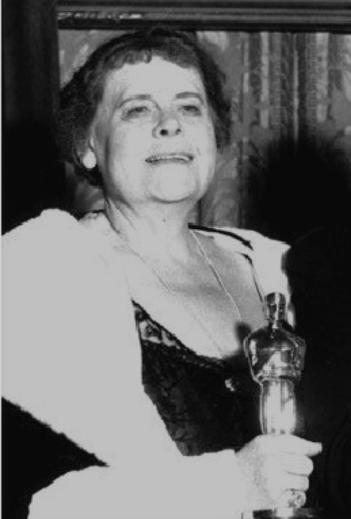 Marie Dressler winning her Oscar for Min and Bill. Origins of gown unknown. Marie wore a black sleeveless gown with lace paneling in front. Over her dress, she donned a matching black jacket with wide collar.