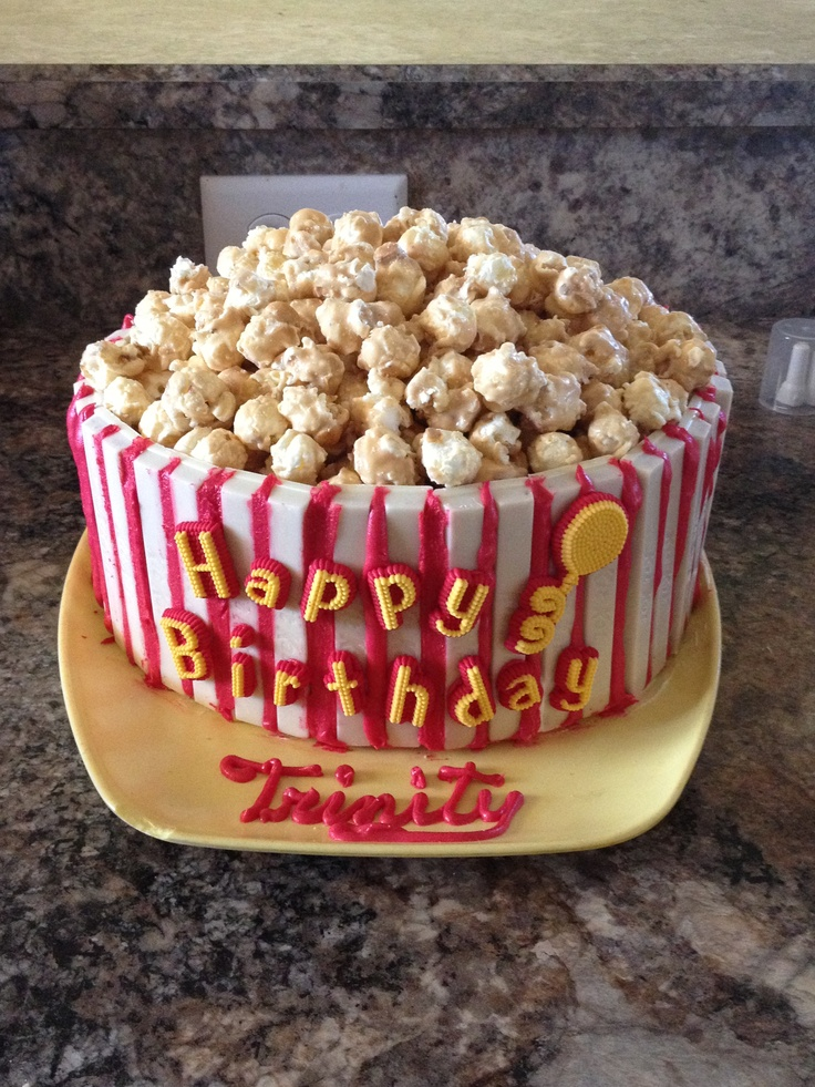 """""""Popcorn Bucket"""" Cake 2 circle cakes on top of each other, iced with frosting, white choco Kit Kats around it, red icing, and then filled to the top with Crunch-N-Munch. """"Popcorn Bucket"""""""