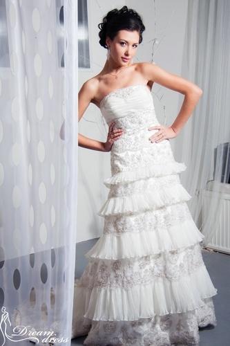 BRITANI  Описание:  Силуэтное свадебное платье выполнено из атласа и кружева. Верхняя часть представляет собой облегающий корсет со шнуровкой. Прямая свободная юбка со шлейфом выполнена в виде воланов в пять ярусов. Платье красиво украшено вышивкой серебряной нитью, бисером, бусинками, стразами, кристаллами Swarovski и паетками. Универсальный стиль платья позволяет использовать различные свадебные аксессуары и украшения. http://www.dream-dress.ru