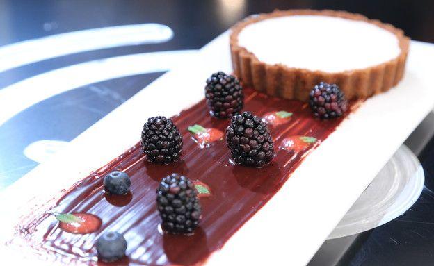 מתכון לעוגת גבינה של מיכל אפשטיין ממאסטר שף. עוגת גבינה לימונית ועשירה על בסיס עוגיו  לוטוס, עם ציפוי שמנת ותוספת של גנאש שוקולד מריר בהגשה
