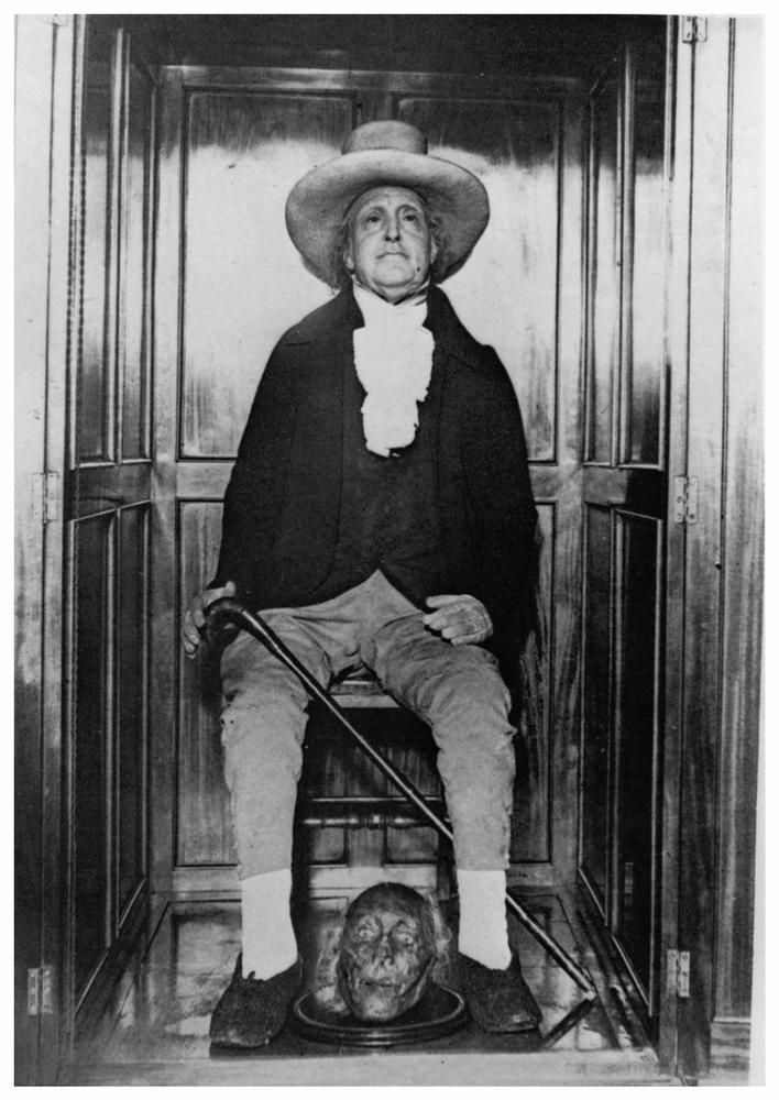 Jeremy Bentham's mummified body and wax head, with his actual head at his feet.