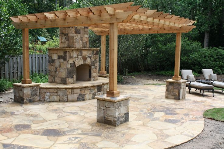 Flagstone Patio With Outdoor Fireplace And Pergola With
