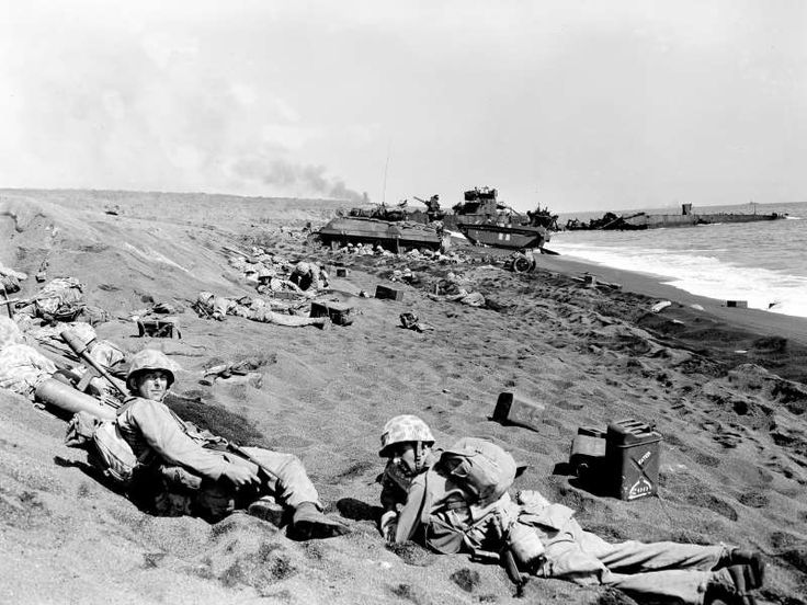 U.S. Marines of the Fourth Division shield themselves in abandoned Japanese trench and bomb craters ... - AP Photo/Joe Rosenthal