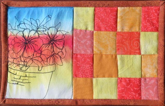 Petunias in a baskets drawn in thread.