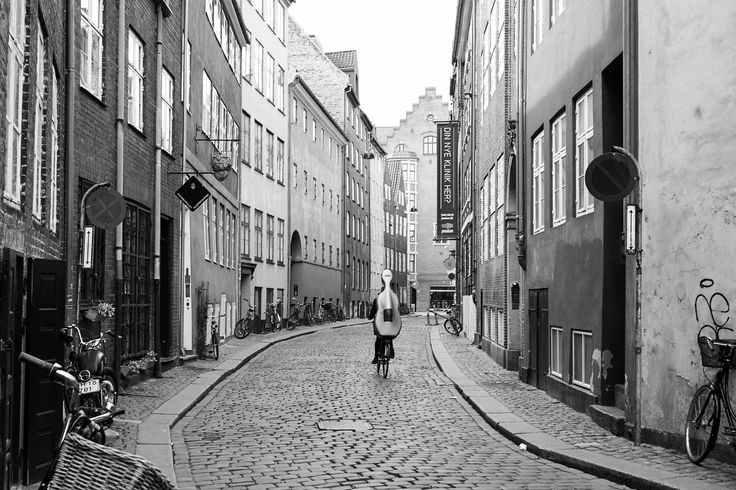 In the City of Bicycles, Copenhagen, a musician is riding along the cobblestone streets with a cello.