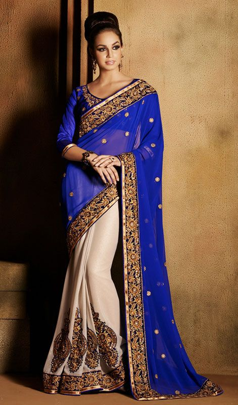 Trendy blue and off white georgette half n half sari is perfect for any evening party requirement. Sari is garnished with golden woven lace, golden silk thread embroidered foliage pattern border, crystal stones and patched motifs in the hem of the first off white half of the sari and scattered floral motifs in the blue half of the sari which gives it an elegant effect. The sari pairs with matching stitched blouse as shown in the picture. #DesignerSaree