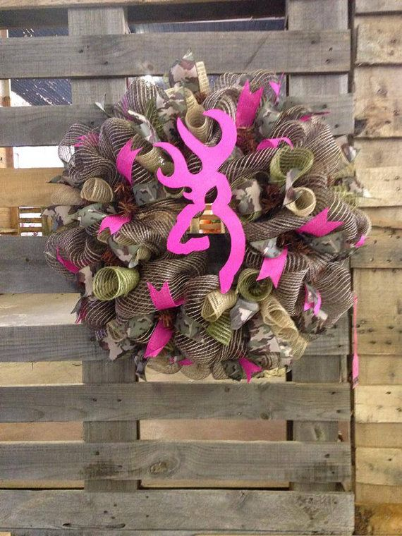 This 26 camouflage wreath is a brown, tan, and green burlap deco mesh with accents of hot pink and camouflage ribbon. The Browning symbol is
