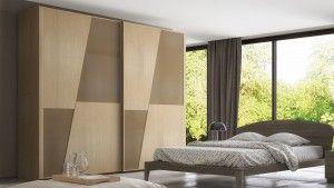 Armadio in legno massello a due ante scorrevoli e pannelli trapezoidali a specchio tono su tono.