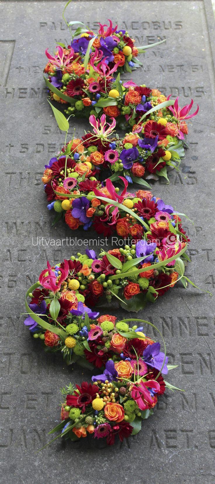 Uniek • bloemenslinger • kistbedekking • kleurrijk • rouwstuk • rouwbloemwerk • Gloriosa • Vanda • Santini • Craspedia • Gerbera • Trosroos • Hypericum • Thypha •
