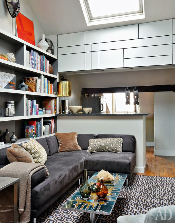 Гостиная. На старом деревянном полу — ковер по дизайну Дэвида Хикса. Рядом с диваном из нубука — винтажный керамический столик. Стеллажи сделаны на заказ из МДФ.