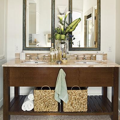 If you have open shelves, use large baskets to corral small toiletries and accessories. Here, each sink has its own dedicated bin to keep his-and-hers from getting jumbled together. | SouthernLiving.com