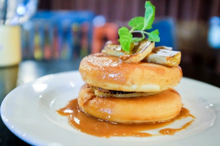 Buttermilk pancakes with thick but tender, a triumph of texture, tastily layered with either sauteed bananas glazed in butterscotch or wild berries with cream, bathed in syrup & butter at The Bee, Publika.