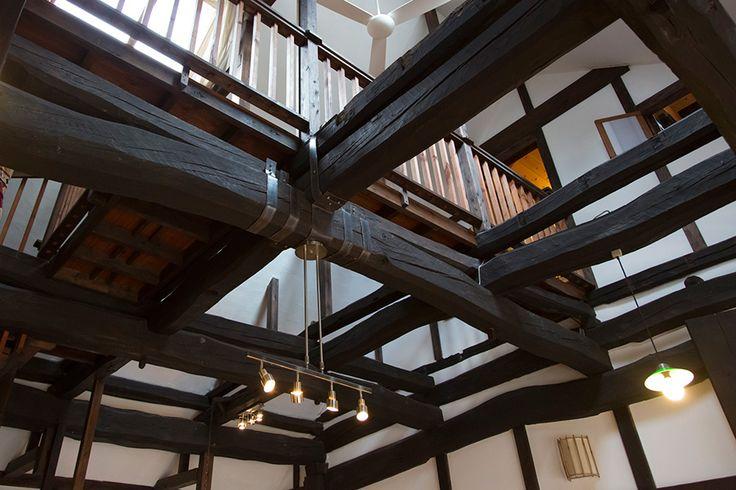 井桁組みの頑丈な梁が、大きな空間を支える。年季の入った梁の渋い色が、白い漆喰の壁に映える。