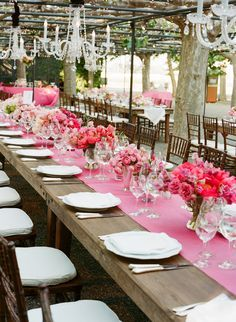 Rustic wood with pink accents and crystal chandeliers make for a chic outdoorsy wedding