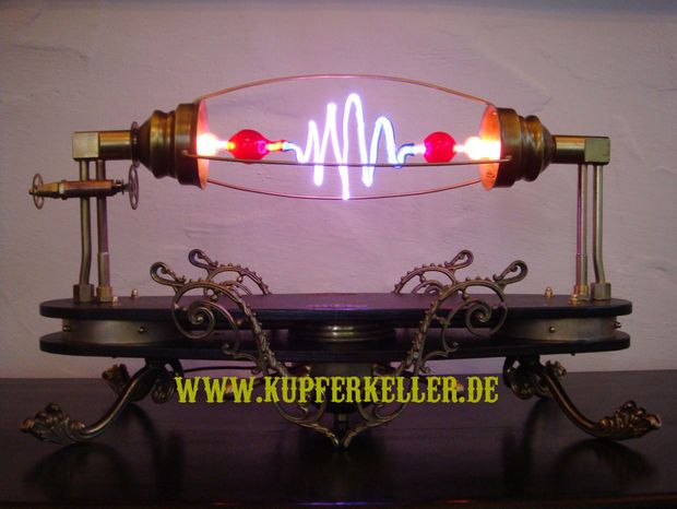 """DIY project! """"Aetheria Circumducitur"""". A high Voltage Lamp with a """" Neon Geissler Tube """". Driven with a Tesla Generator and 5000 Volt. A rotating Cage turns around the Geissler Tube."""